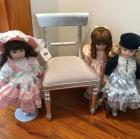 "Chair and three 15"" porcelain dolls"