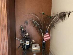 Holy Bible, peacock feathers in vase, floral arrangement