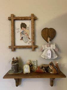 Wall shelf, framed needlepoint, figurines