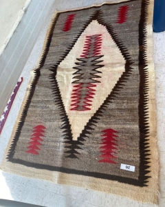 Native American rug with brown, red and cream colors