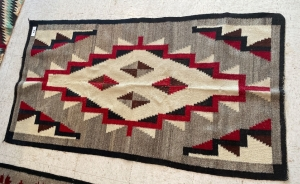 Native American rug with red, black, cream and brown colors
