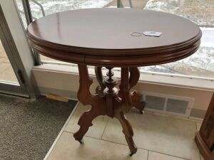 Antique oval walnut lamp table w/ porcelain casters
