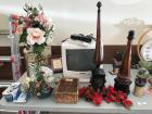 Panasonic TV and VHS player, floral items, horse figures, Ford clock, Precious Moments Bell, misc on top of table